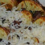 Parmesan über den Kartoffelgratin streuen